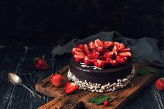Chocolate cake with fresh strawberries on a dark background. Selective focus. Food mood stock photo