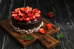 Chocolate cake with fresh strawberries on a dark rustic background. Selective focus. Dark food photo. royalty free stock photos
