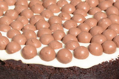 Chocolate cake with frosting covered in maltesers. Chocolate cake with frosting covered in chocolate maltesers royalty free stock photography