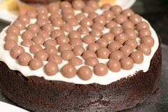 Chocolate cake with frosting covered in maltesers. On stand stock photos