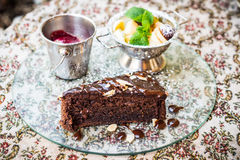 Chocolate cake, fruit and ice cream. Piece of chocolate cake with fruit and ice cream is on the glass tray on the table stock photography
