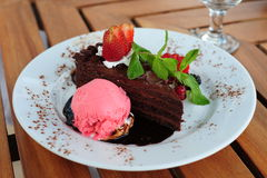 Chocolate cake with garnish. Delicious fresh chocolate cake with various berries, mint leaf and strawberry ice cream on a white plate stock photo