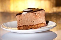 Chocolate cake on gold background. Yummy chocolate cake on shiny gold background. Shallow focus Royalty Free Stock Image
