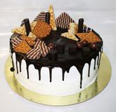 Chocolate cake on a gold substrate. Decorated cookies, Savoldo, cream, cake base white chocolate dark Stock Images