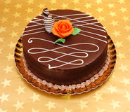 Chocolate cake on golden stars background Stock Image