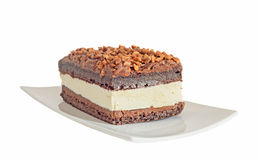 Chocolate cake with hazelnut and white cream, nuts, white plate, Royalty Free Stock Photo