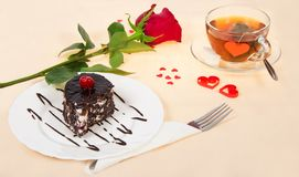 Chocolate cake, hot tea and red rose Stock Photo