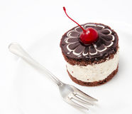 Chocolate cake icing with cherry on the plate isolated on a whit Royalty Free Stock Image