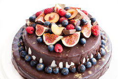 Chocolate cake with icing, decorated with fresh fruit Royalty Free Stock Photos