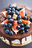 Chocolate cake with icing, decorated with fresh fruit Stock Photos