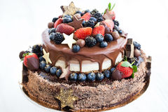 Chocolate cake with icing, decorated with fresh fruit royalty free stock images