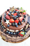 Chocolate cake with icing, decorated with fresh fruit Royalty Free Stock Photography