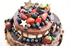 Chocolate cake with icing, decorated with fresh fruit Stock Photo
