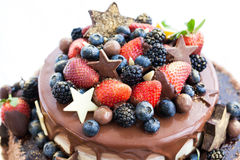 Chocolate cake with icing, decorated with fresh fruit Stock Image