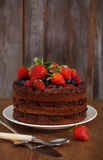 Chocolate cake with icing and fresh berry. On wooden background Royalty Free Stock Photo