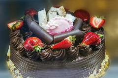 Chocolate cake with icing and fresh strawberry.  Stock Images