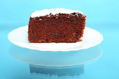 Chocolate cake with icing sugar on blue Stock Images
