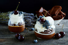 Chocolate cake in jar with whipped cream, ice cream and berries Stock Image