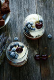 Chocolate cake in jar with whipped cream, ice cream and berries Stock Images