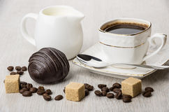 Chocolate cake, jug milk, pieces of sugar and coffee cup. On wooden table Stock Image