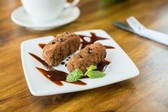 Chocolate cake kartoshka and cappuccino on a wooden table Stock Image