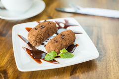 Chocolate cake kartoshka and cappuccino on a wooden table Royalty Free Stock Photos