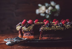 Chocolate cake with marzipan and raspberries. On a wooden table Royalty Free Stock Image