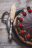 Chocolate cake with marzipan and raspberries. On a wooden table Stock Photo