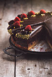Chocolate cake with marzipan and raspberries. On a wooden table Stock Photography