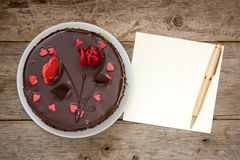 Chocolate cake with note paper and pen Royalty Free Stock Photos