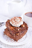Chocolate cake with nuts and whipped cream. In plate Stock Photography