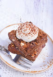 Chocolate cake with nuts and whipped cream. In plate Stock Photo