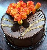 Chocolate tart. With orange roses on the top royalty free stock photography