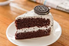 Chocolate Cake with oreo and whipped cream on white plate and wood table has ready to served.
