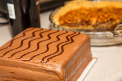 Chocolate Cake with Pecan Pie and Wine Bottle in Background Royalty Free Stock Photography