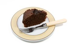 Chocolate cake on a plate. Slice of chocolate cake on a plate isolated over white Royalty Free Stock Image