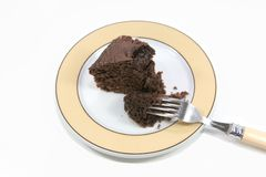 Chocolate cake on a plate. Slice of chocolate cake on a plate with a chunk on a fork Royalty Free Stock Photography