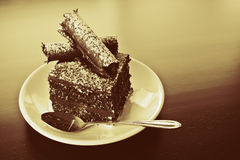 Chocolate cake on plate. Piece of chocolate cake on a serving plate with spoon Royalty Free Stock Images