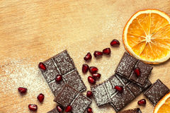 Chocolate cake with pomegranate seeds on a wooden table Royalty Free Stock Photography