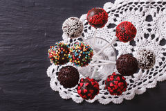 Chocolate cake pops with candy sprinkles on a lace doily. horizo Stock Image