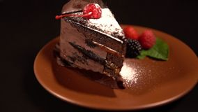 Chocolate cake with pouring vanilla powdered sugar. Close-up studio shot of a piece of chocolate layered cake served on a brown saucer with fresh berries and stock footage