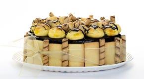 Chocolate cake with Profiteroles. An elegant and delicious gourmet chocolate cake with profiteroles on top on white background Royalty Free Stock Photos