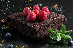 Chocolate cake with raspberries, blueberries, orange zest and peppermint. Chocolate cake with raspberries, blueberries, orange zest and peppermint Royalty Free Stock Photography