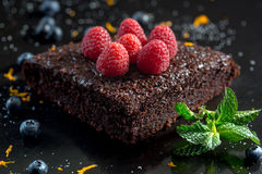 Chocolate cake with raspberries, blueberries, orange zest and pi. Permint Stock Image