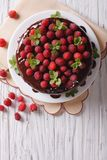 Chocolate cake with raspberries and mint on the table vertical t. Chocolate cake with fresh raspberries and mint on the table. vertical top view Royalty Free Stock Image