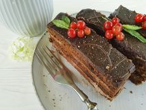 Chocolate cake, red currant, mint, flower plate on white wooden. Nutrition Royalty Free Stock Images