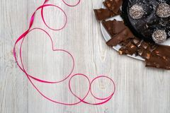 Chocolate cake and Red ribbon heart. Flat lay. Valentine`s Day celebration concept. Chocolate cake and Red ribbon heart on wooden table. Flat lay. Valentine`s royalty free stock photo