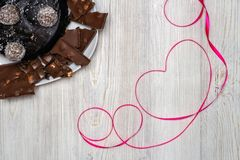 Chocolate cake and Red ribbon heart. Flat lay. Valentine`s Day celebration concept. Chocolate cake and Red ribbon heart on wooden table. Flat lay. Valentine`s royalty free stock image