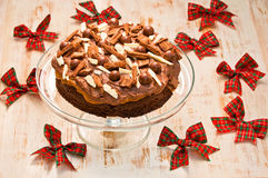 Chocolate cake with ribbons. Delicious chocolate cake smothered in ganache, decorated with red and green ribbons Royalty Free Stock Photos