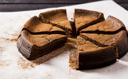 Chocolate cake with ricotta. Chopped into pieces, on a dark wooden background Stock Photo